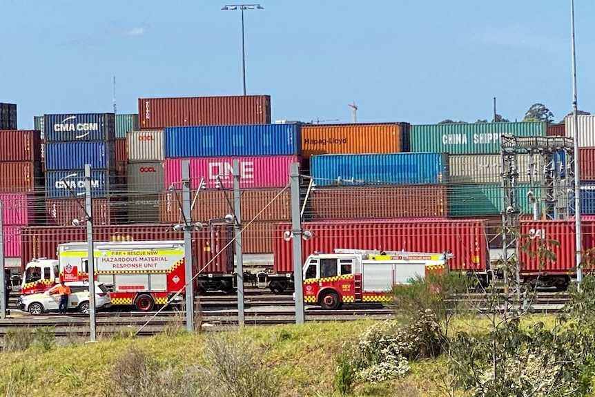 Stacks of shipping containers and fire trucks in the foreground,