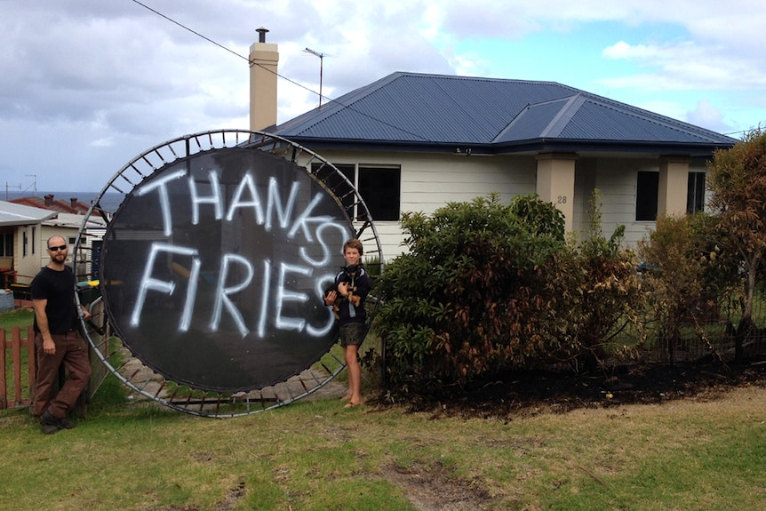 Man and boy standing next to Thank You Firies sign painted on trampoline