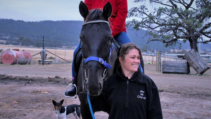 A woman stands next to a horse with a rider, holding the reins  on a rural property.