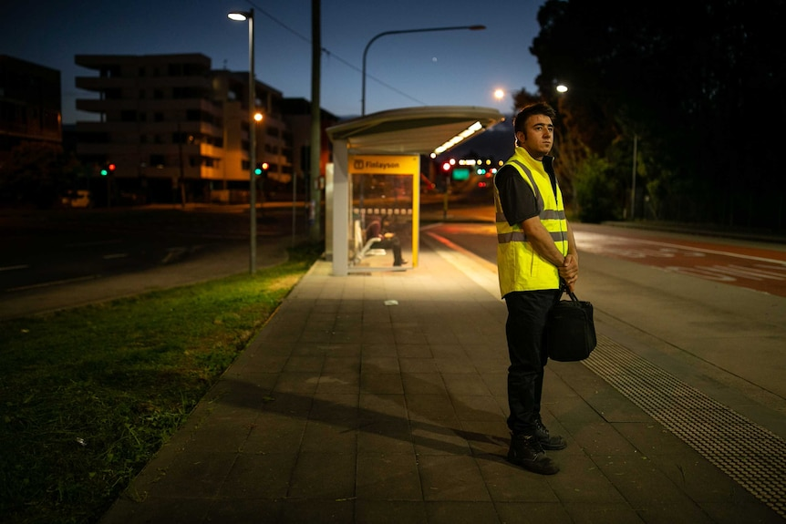 A man stands at a bus stop in the early morning.
