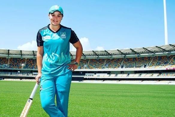 Ash Barty on a cricket pitch holding a bat.