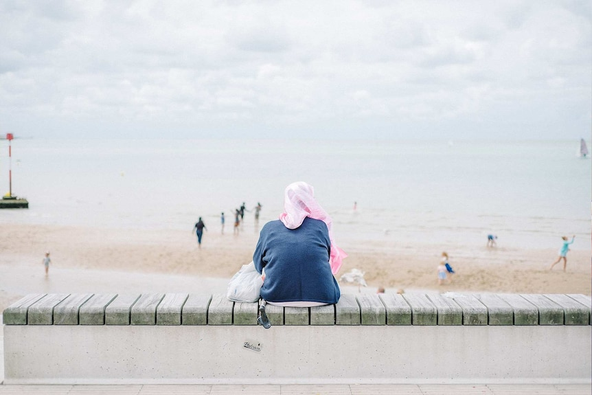 Woman wearing a pink hijab and appearing lonely while looking out over a beach on an overcast day to depict loneliness.