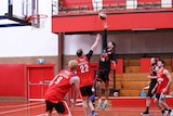 basketball player attempts slamdunk while opponent  attempts to block and other players stand by