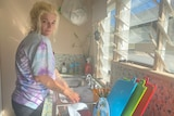A woman with blonde hair washes dishes in a sink in her kitchen, near open louvered windows.