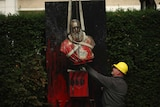 A bust of Belgium's King Leopold II, is hoisted off of its plinth by a crane as it's removed from a park in Ghent, Belgium.