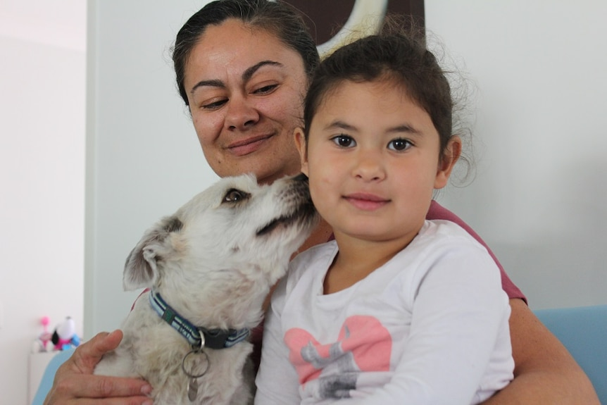Mother, four-year-old daughter and dog sit closely together, with dog licking daughter's face.