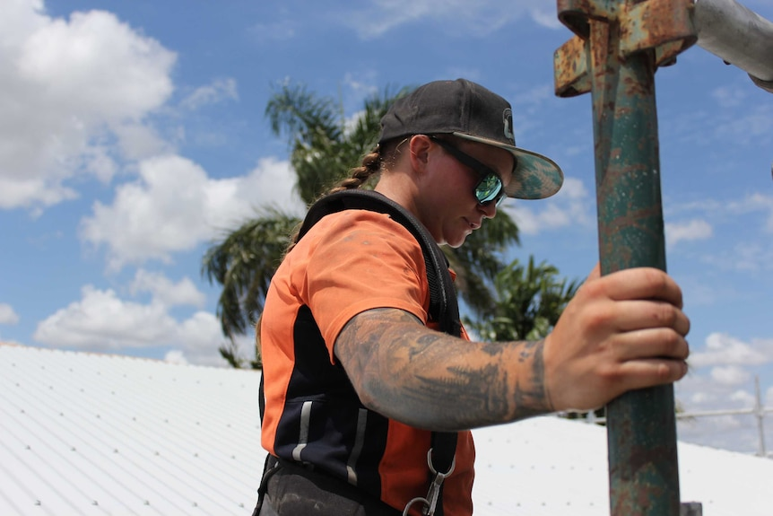 Carpentry apprentice Emily Bailey clutches scaffolding while on a roof, with blue skies and a palm tree behind her.