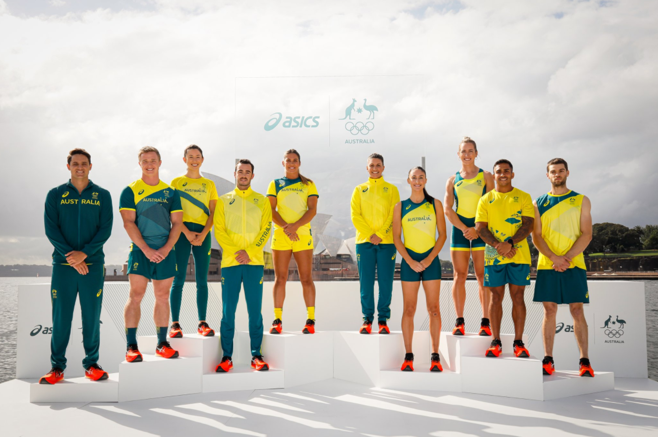 A group of athletes standing on a podium at the unveiling of a team uniform.