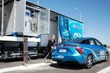 A woman refuels a hydrogen fuel cell car