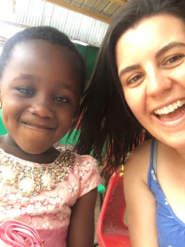 A young Caucasian woman takes a smiling selfie with a young girl of African appearance.