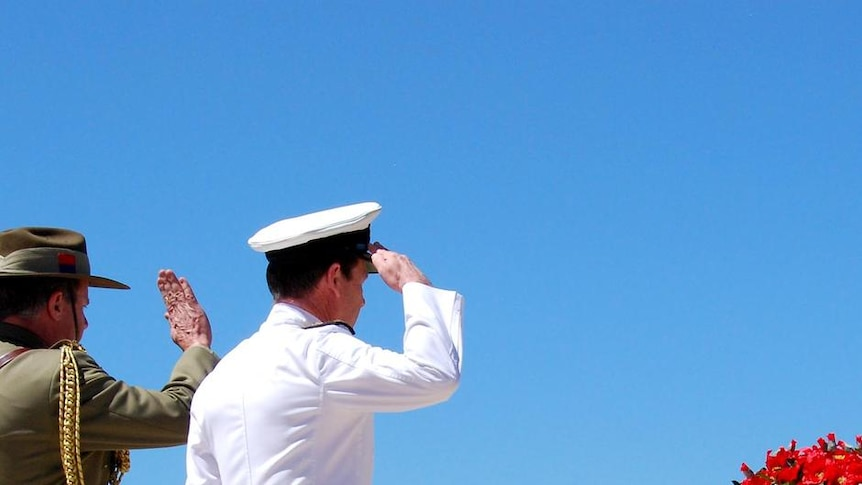 Members of the Armed Services salute the Stone of Remembrance outside the Australian War Memorial