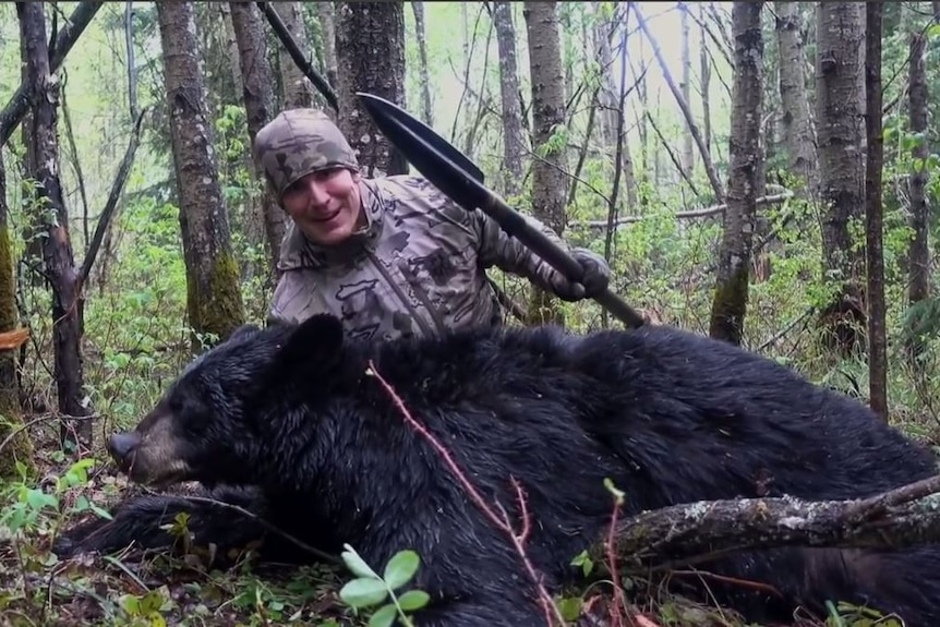 Hunter Josh Bowar poses with a bear he killed while holding a spear