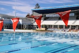 Flags hanging across a large swimming pool.