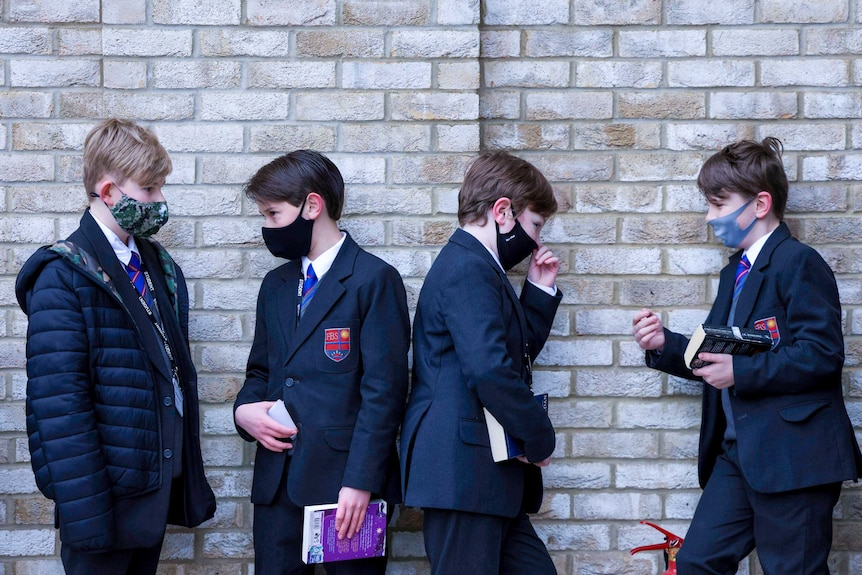 Four boys in blazers and face masks leaning against a brick wall