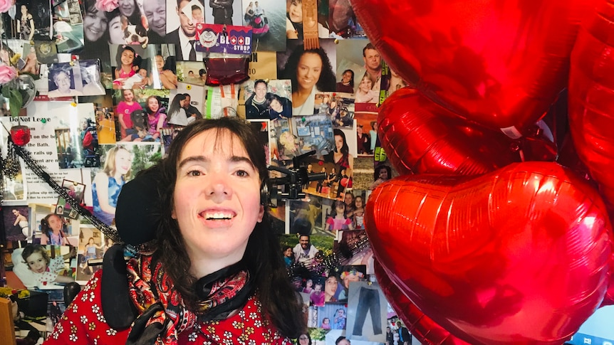 Kim Hopton smiling pictured with red heart baloons.