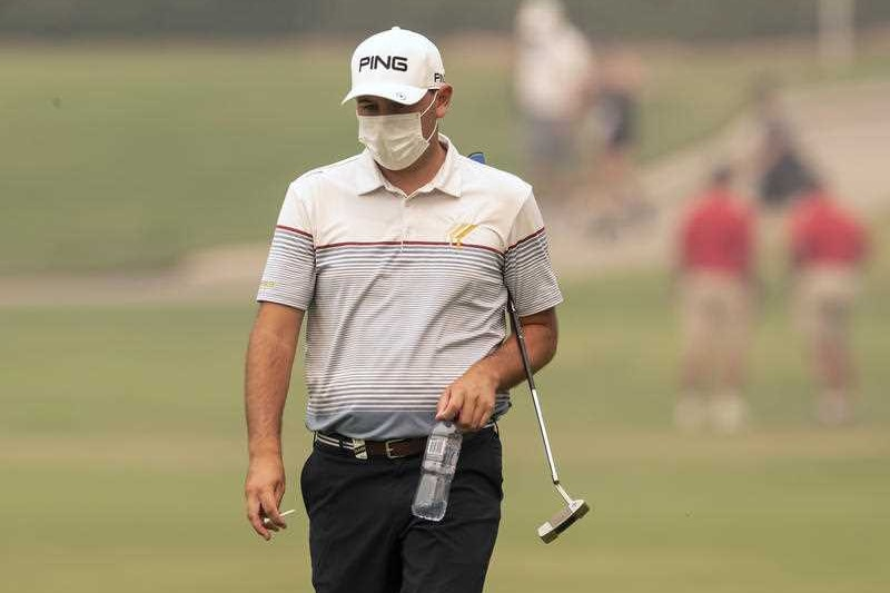A golfer on a course with a face mask