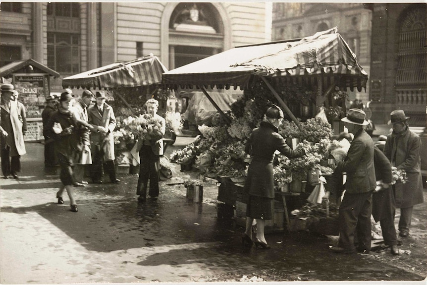 An old photo of a man holding flowers, people bustling around