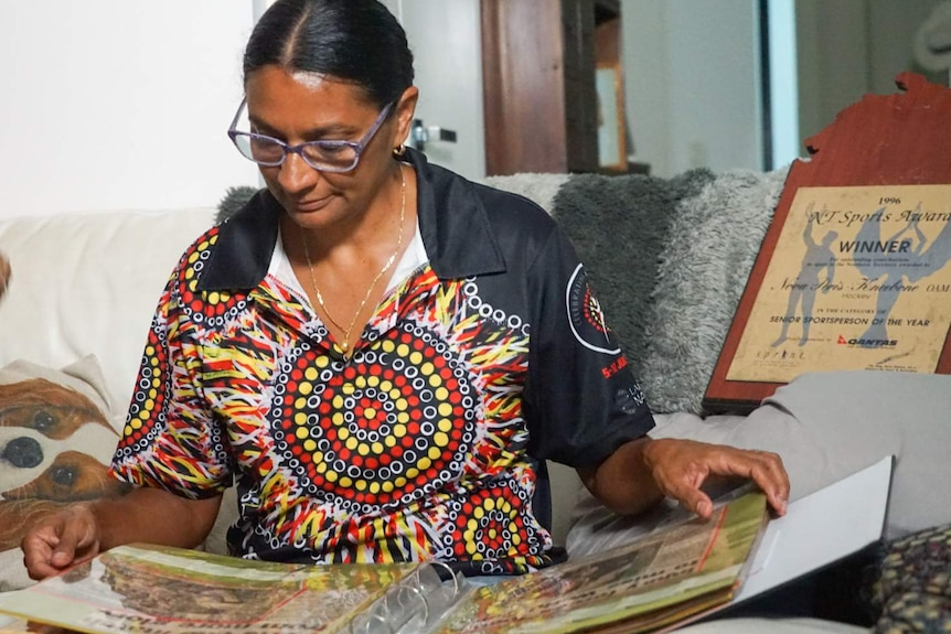 Nova looks at a photo album, wearing a bright t-shirt with an Indigenous pattern on it.