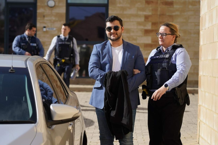Tyson Vacher being escorted by a police woman into an unmarked car.