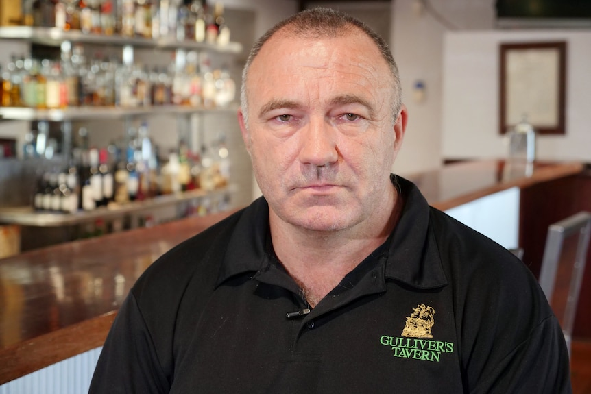 A man wearing a black t-shirt sits in a bar and looks towards the camera.
