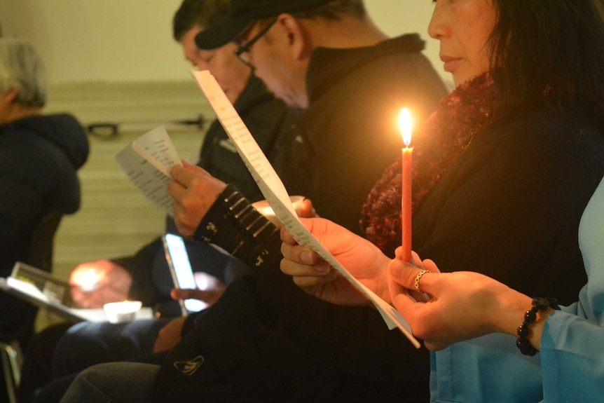 A woman holds a candle and reads music