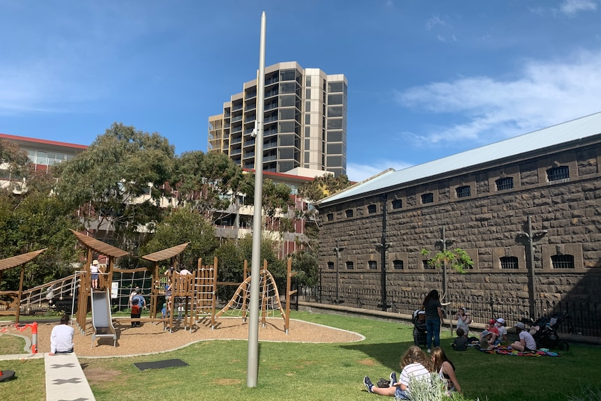 A playground with children and families around it, near bluestone Pentridge walls, with tall apartment block in background.