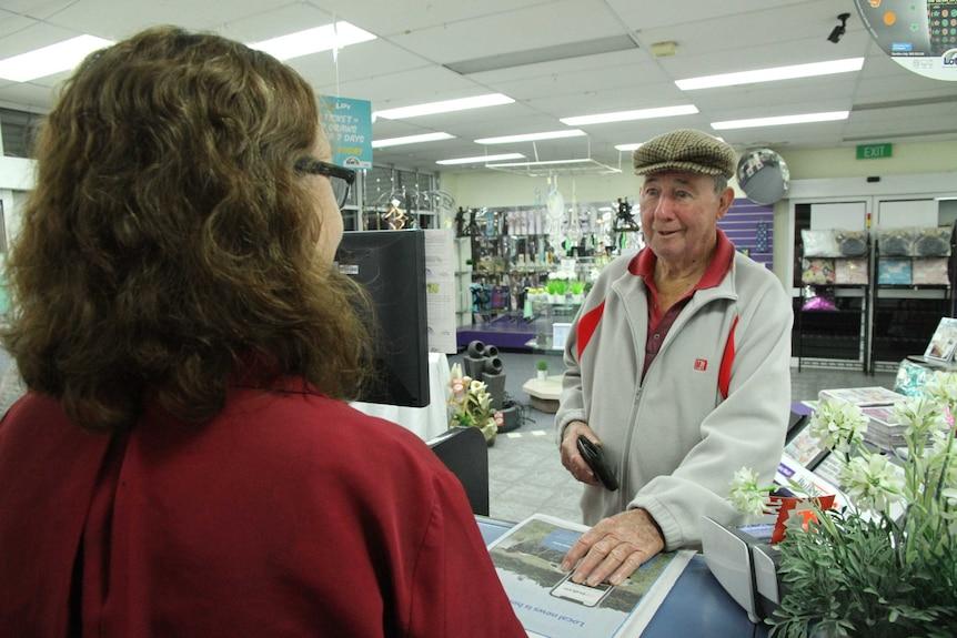 An elderly gentleman buys a newspaper from a woman at a newsagent