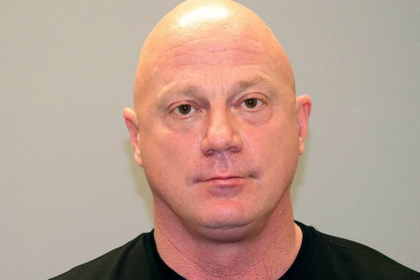 a mugshot of Larry Rendall Brock Jr wearing a black shirt with a shaved head