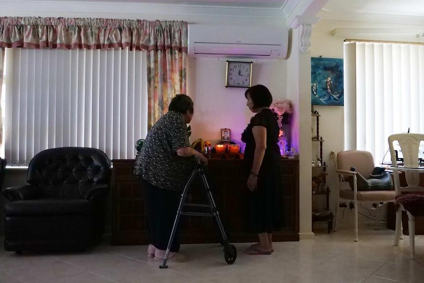 Two women around a shrine.