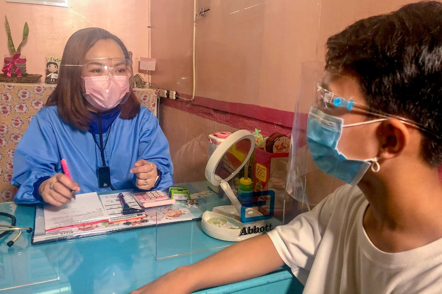 A young Filipina woman in a face mask and scrubs talks to a boy across a table