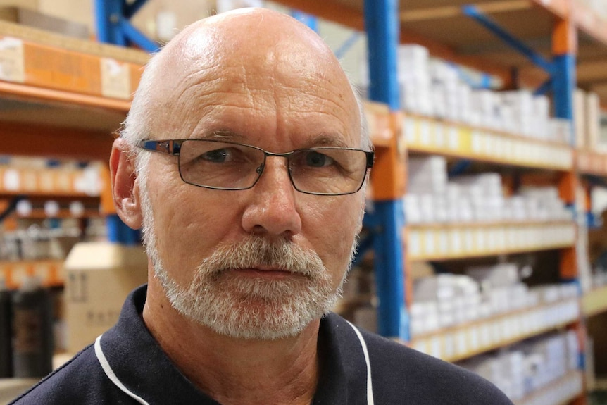 A man with glasses wearing a blue polo shirt stands in a warehouse.