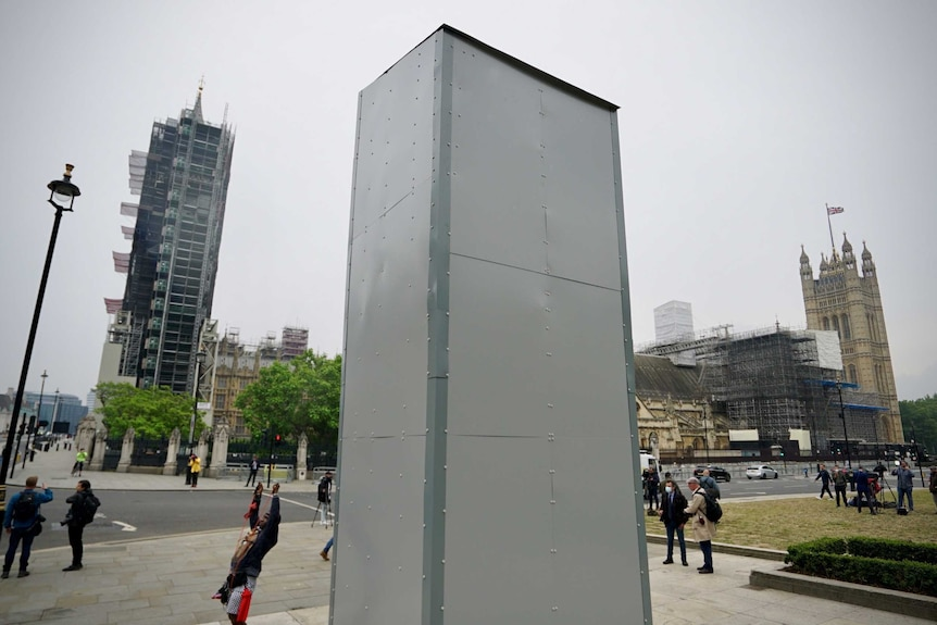 Pale grey hoarding covers the statue of Winston Churchill.