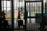 A small group of young men playing basketball on a court inside Darwin's Don Dale youth detention centre, 2017.