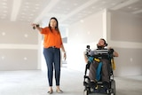 A man is a wheelchair inside a home yet to be painted next to a woman walking and pointing
