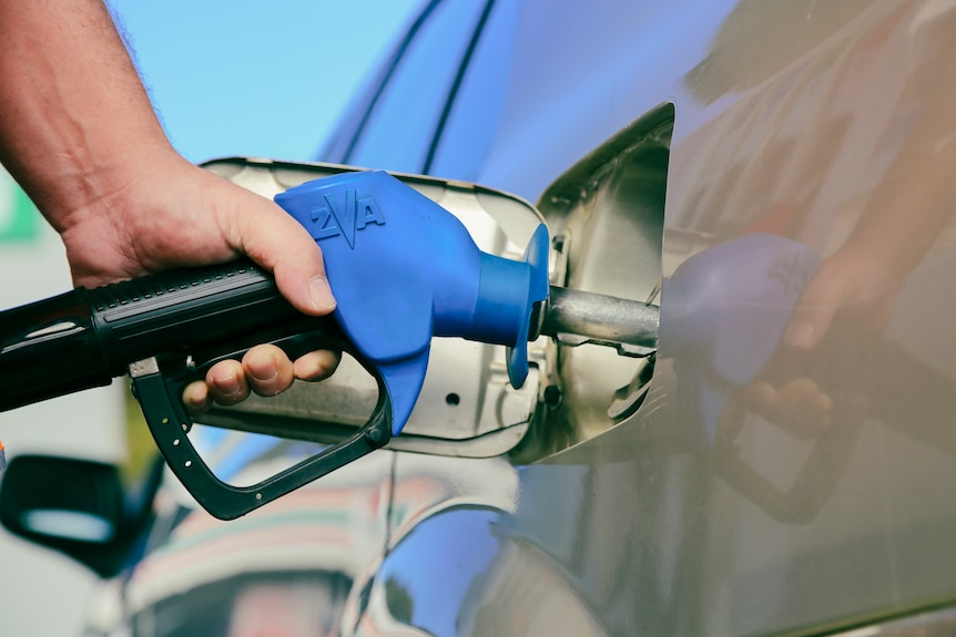 A man holds a petrol bowser while filling up his car.