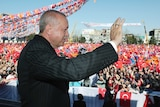 Erdogan waves to a large crowd of supporters waving flags.