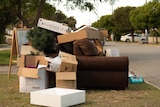 Sofa, cardboard boxes, tree, easel on verge for collection.