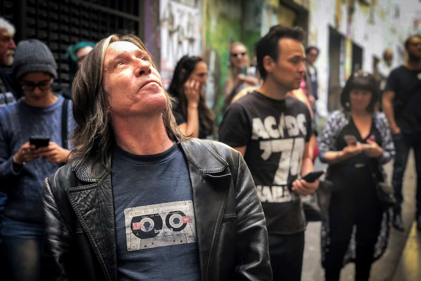 A man looks up at an artwork of Bon Scott in Melbourne's AC/DC lane.
