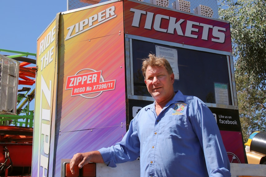 A man stands in front of a carnival ride ticket booth