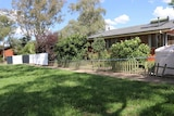 Australian Federal Police barrier can be seen outside the house, also trees lined up along fence.
