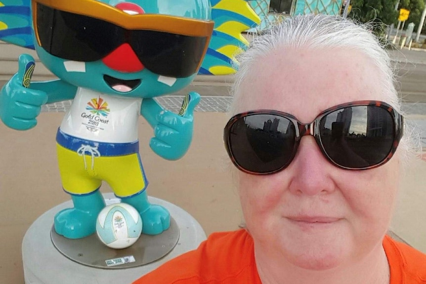 A grey haired lady in an orange t-shirt smiles as she takes a selfie
