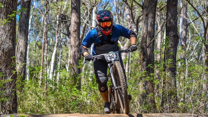 A mountain bike rider rides along a bush track.