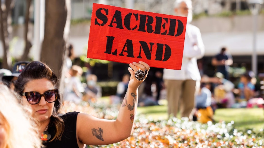 A protestor holds a sign saying 'sacred land' at a Rio Tinto protest.
