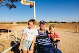 A man in his wheelchair with his daughter and son standing beside him