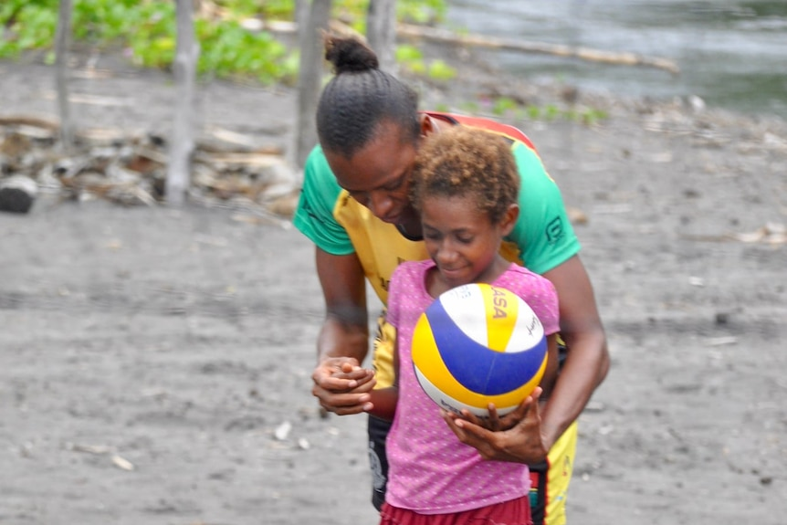 Young girl hold volleyball in left hand as older woman stands behind her, cradling her arms.