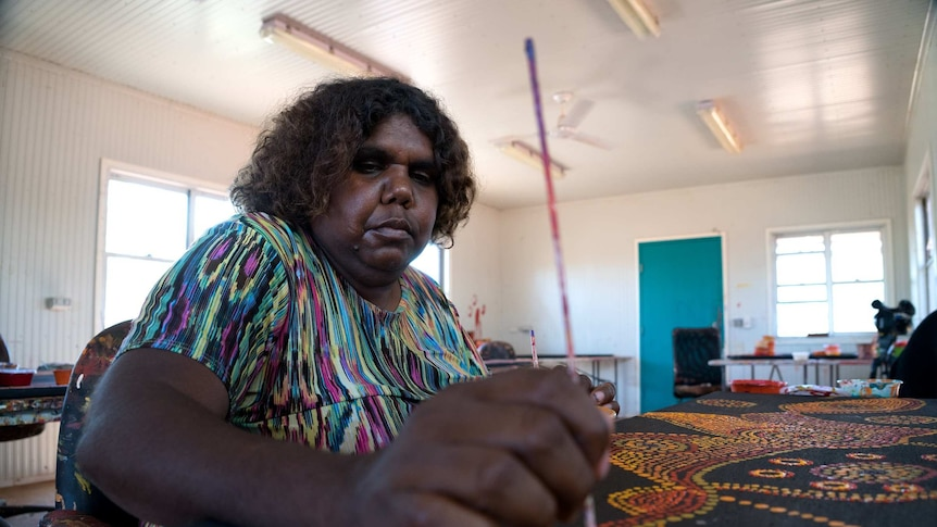 An Indigenous woman paints spots onto a painting in a art workshop.