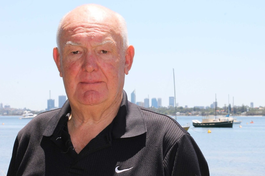 Mick Buckley stands in front of a harbour with boats in the background