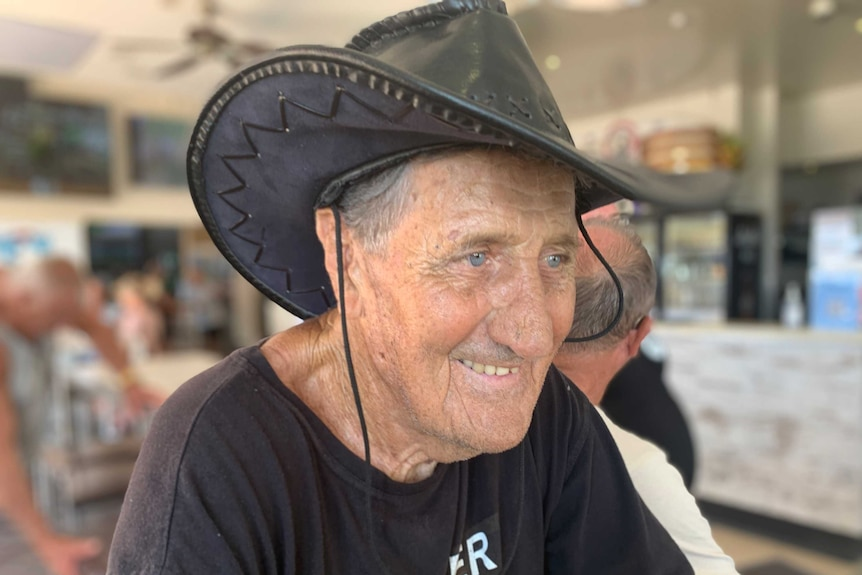 A man wearing an Akubra-style hat smiles in a bar.