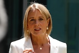 Kristina Keneally wearing a white blazer and blouse mid-sentence standing in a bright courtyard on a sunny day