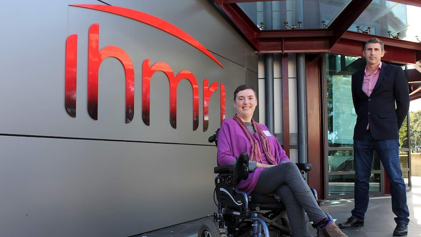 A woman in a wheelchair and a man standing outside the Illawarra Health and Medical Research Institute